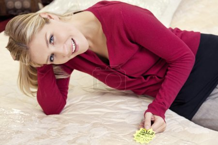 Portrait of a happy young woman reclining on mattress with price tag