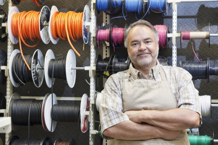 Photo for Portrait of a happy mature salesperson standing in front of electrical wire spool with arms crossed in hardware store - Royalty Free Image