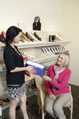 Happy mature customer taking footwear box from mid adult female salesperson in shoe store
