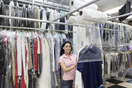 Photo for Portrait of a happy mid adult woman putting plastic to dry cleaned clothes in laundry - Royalty Free Image
