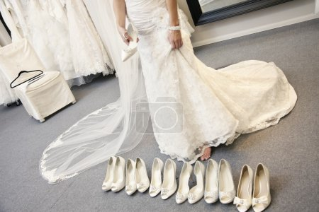Photo pour Petite section de jeune femme debout avec une variété de chaussures dans la boutique nuptiale - image libre de droit