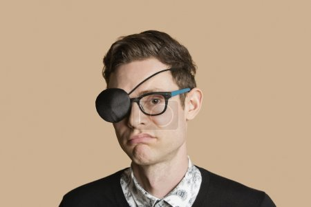 Portrait of a man wearing eye patch on glasses over colored background