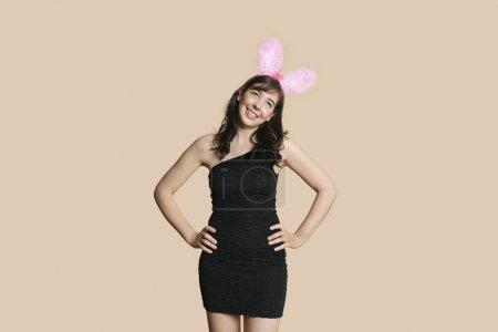 Photo pour Belle jeune femme en robe noire avec des oreilles de lapin à la recherche de suite sur fond coloré - image libre de droit