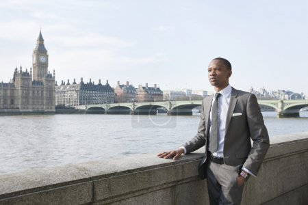 Young African American businessman looking away with hand in pocket