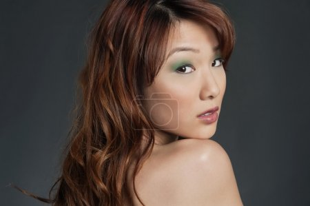 Beautiful young Chinese woman looking back over colored background