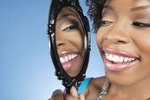 Close-up of a young woman looking at herself in mirror and smiling over colored background
