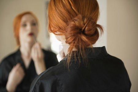 Photo pour Vue arrière de la jeune femme appliquant maquillage - image libre de droit