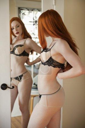 Photo pour Belle jeune femme ajustant sa lingerie devant le miroir - image libre de droit