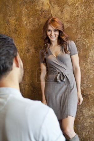 Young woman looking at man while standing against wall