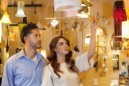 Young couple looking at price tag of lighting equipment in lights store