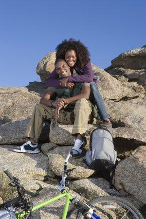 Woman Embracing Man While Sitting On Rocks