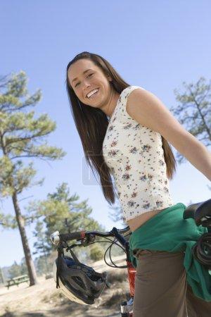 Photo pour Vue en angle bas d'une femme heureuse avec VTT - image libre de droit