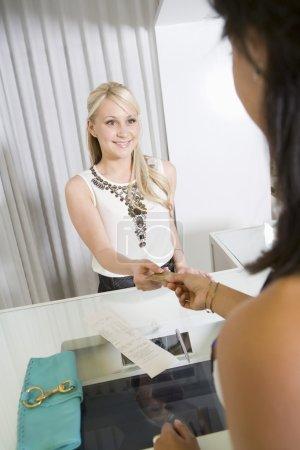 Photo pour Femme payer caissier par le biais de carte de crédit à la caisse en magasin - image libre de droit