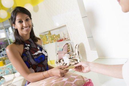 Photo pour Portrait de la belle jeune femme indienne, payer pour le coussin par le biais de carte de crédit au magasin - image libre de droit