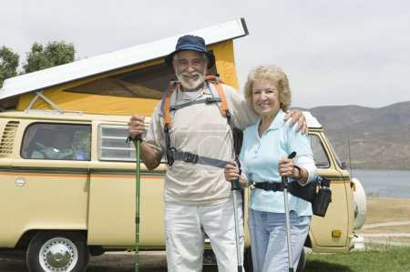 Senior Couple With Walking Poles And Campervan