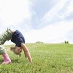 Little girl doing a backbend on grassland against ...