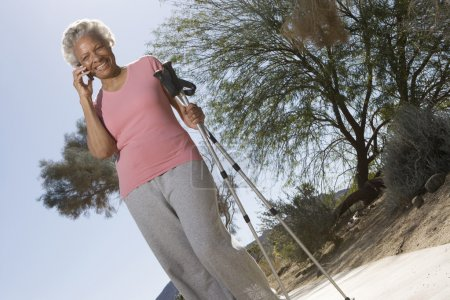 Woman With Walking Poles Using Cell Phone