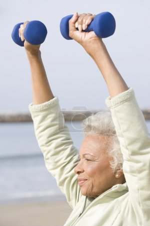 Photo for African American senior woman exercising with dumbbells at beach - Royalty Free Image