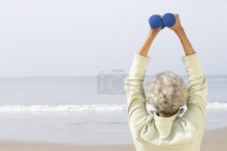 Senior Woman Exercising With Dumbbells On Beach