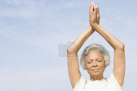 Senior Woman With Eyes Closed In Yoga Pose