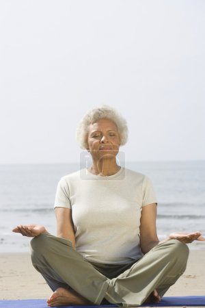 Senior Woman Meditating At Beach