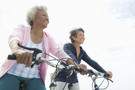Photo for Low angle view of multiethnic senior female friends riding bicycles against sky - Royalty Free Image