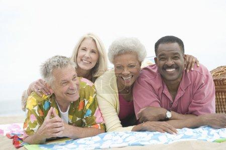 Photo pour Portrait d'amis multiethniques heureux allongés sur le ventre reposant à la plage - image libre de droit