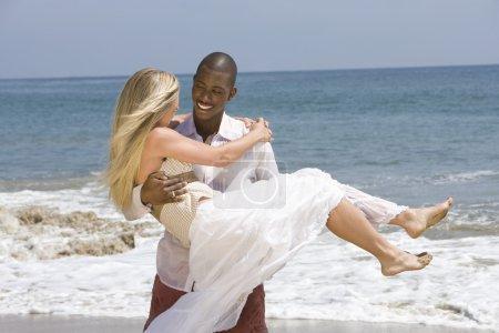 Photo pour Jeune africain-américain transportant sa petite amie dans les bras à la plage - image libre de droit