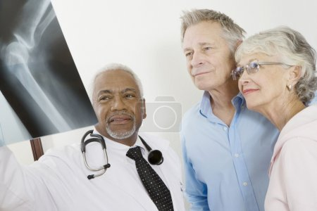 Photo for African American senior male doctor showing x-ray report to patients in clinic - Royalty Free Image