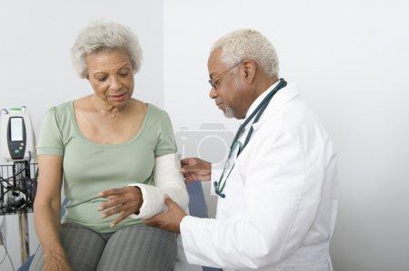 Foto de An African American male doctor checking patient's fractured hand at clinic - Imagen libre de derechos