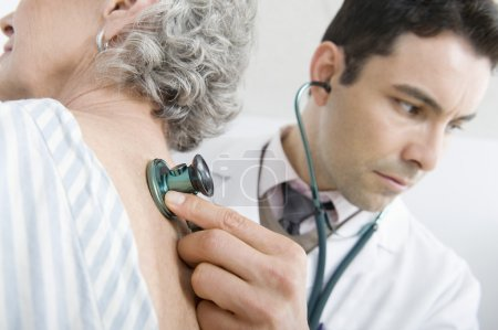 Doctor Examining Patient's Back Using Stethoscope