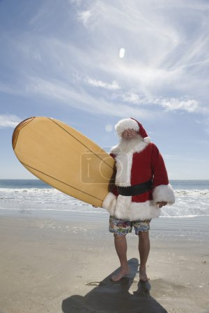 Santa Claus Holding Surfboard On Beach