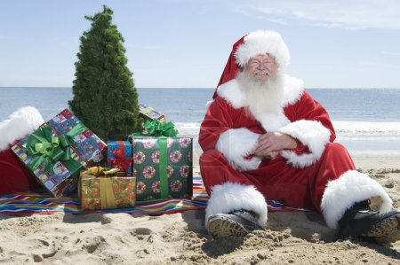Santa Claus With Presents And Tree Sitting On Beach