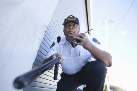 Security Guard Investigates With Walkie Talkie