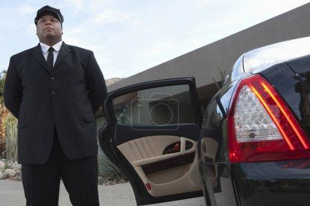 Photo pour Chauffeur de course mixte debout près de la porte ouverte de la voiture sur l'allée - image libre de droit