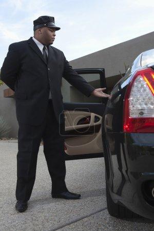 Photo pour Chauffeur mixte sur toute la longueur qui tend la main vers une porte de voiture ouverte - image libre de droit