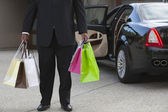 Chauffeur With Shopping Bags In Driveway