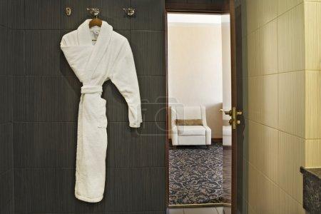 Photo pour Intérieur de la chambre d'hôtel avec peignoir suspendu et la porte ouverte avec vue sur la chambre à côté - image libre de droit