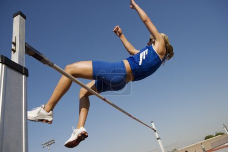 Photo for Female athlete performing high jump against sky - Royalty Free Image