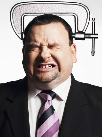 Photo for Stressed businessman with head in vice isolated over white background - Royalty Free Image