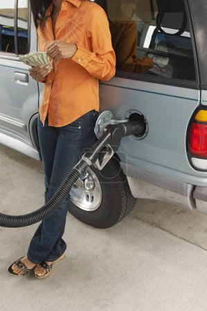 Woman Counting Money At Petrol Pump