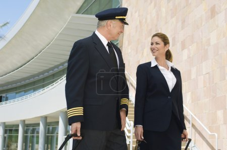 Pilot And Flight Attendant Outside Building