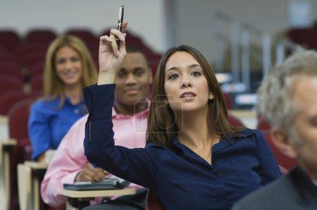 Female executive raising hand