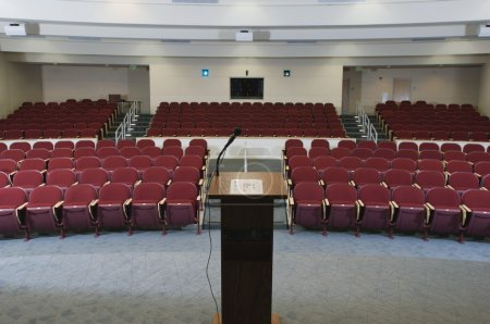 Photo for Red chairs arranged in order and podium at an empty conference auditorium - Royalty Free Image