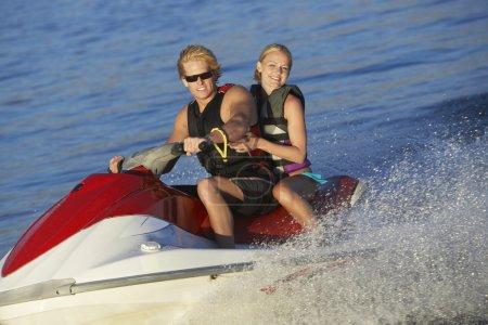 Young Couple Riding PWC On Lake