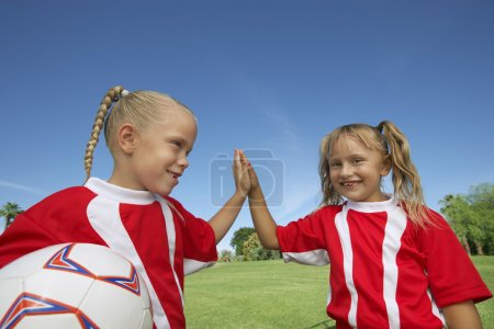 Girls Giving a High-Five On Soccer Field