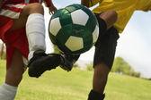 Football Player Tackling Soccer Ball
