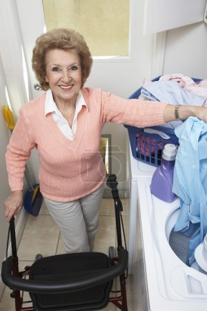 Senior Woman With Laundry By Washing Machine