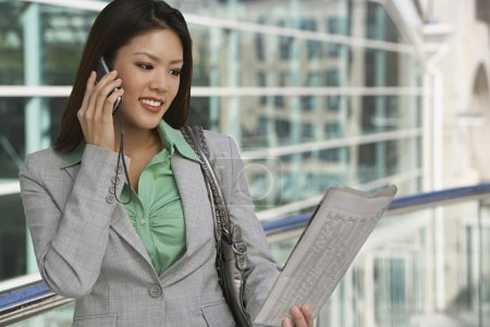 Businesswoman On Call Reading Newspaper