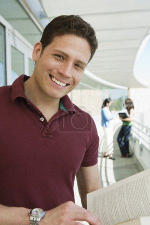 Foto de Retrato de un estudiante varón feliz con mujeres de pie en el fondo - Imagen libre de derechos